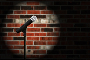 Artistic image of microphone against a rustic brick wall with sp